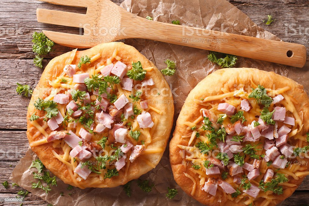 Hungarian pancakes langos with ham and cheese on the table stock photo