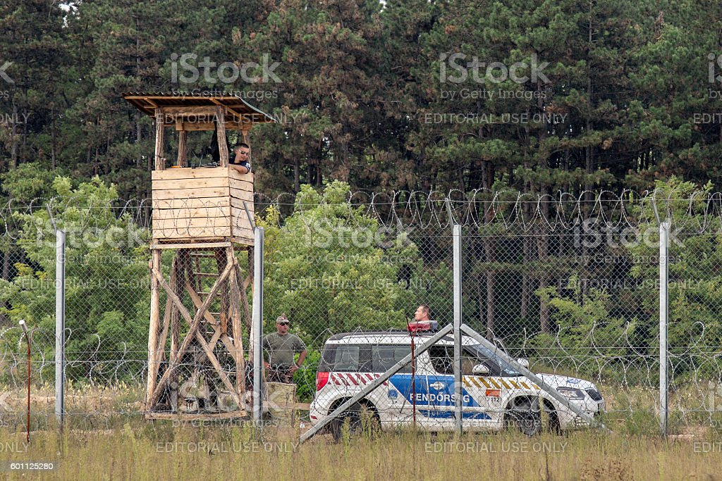 Hungarian policemen watching the Serbia Hungarian border fence stock photo