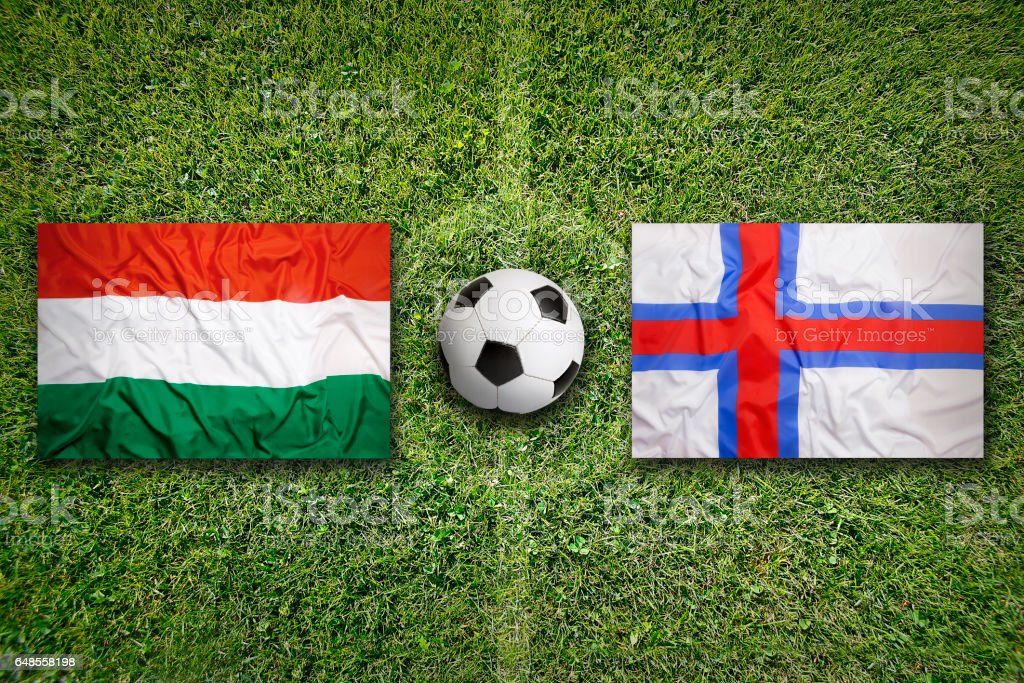 Hungary vs. Faeroe Islands flags on soccer field stock photo
