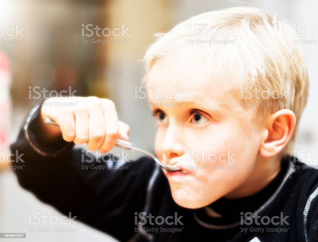 Hungry 7-year-old blond boy eating his breakfast cereal stock photo