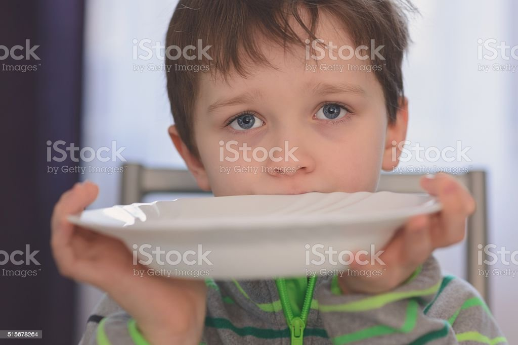 Hungry boy with beautiful eyes waiting for dinner stock photo