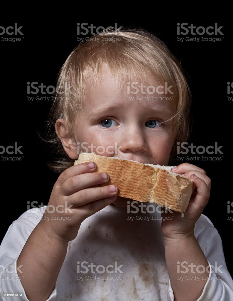 hungry child eating bread stock photo