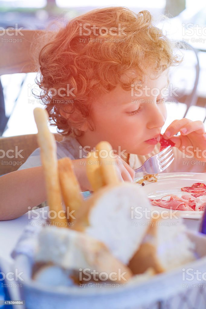Hungry Child eats using fork and hands stock photo