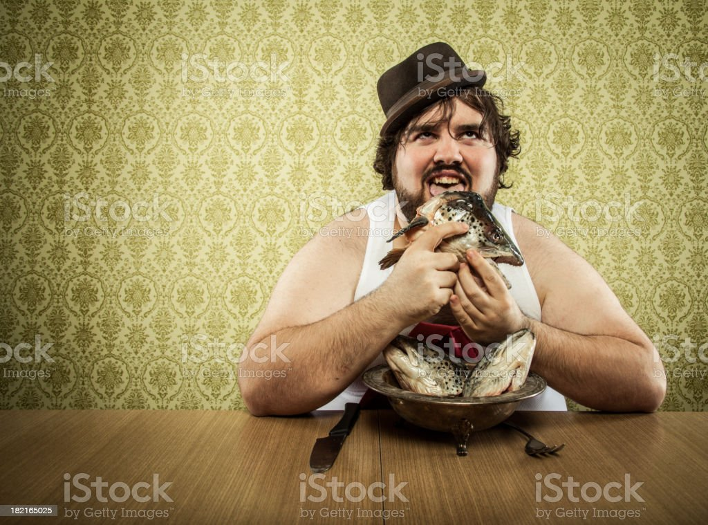 hungry fat man licking fish head soup at wood table stock photo