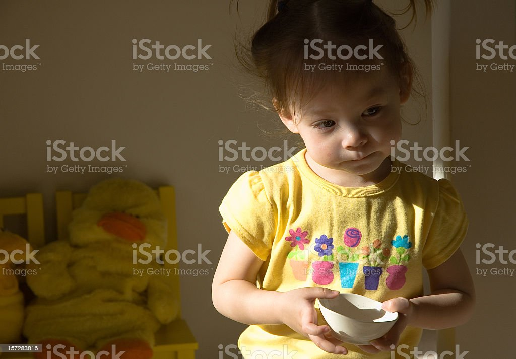 Hungry girl toddler holding empty bowl in her room royalty-free stock photo