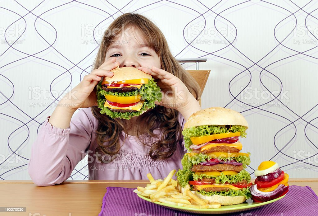 hungry little girl eating a big hamburger stock photo