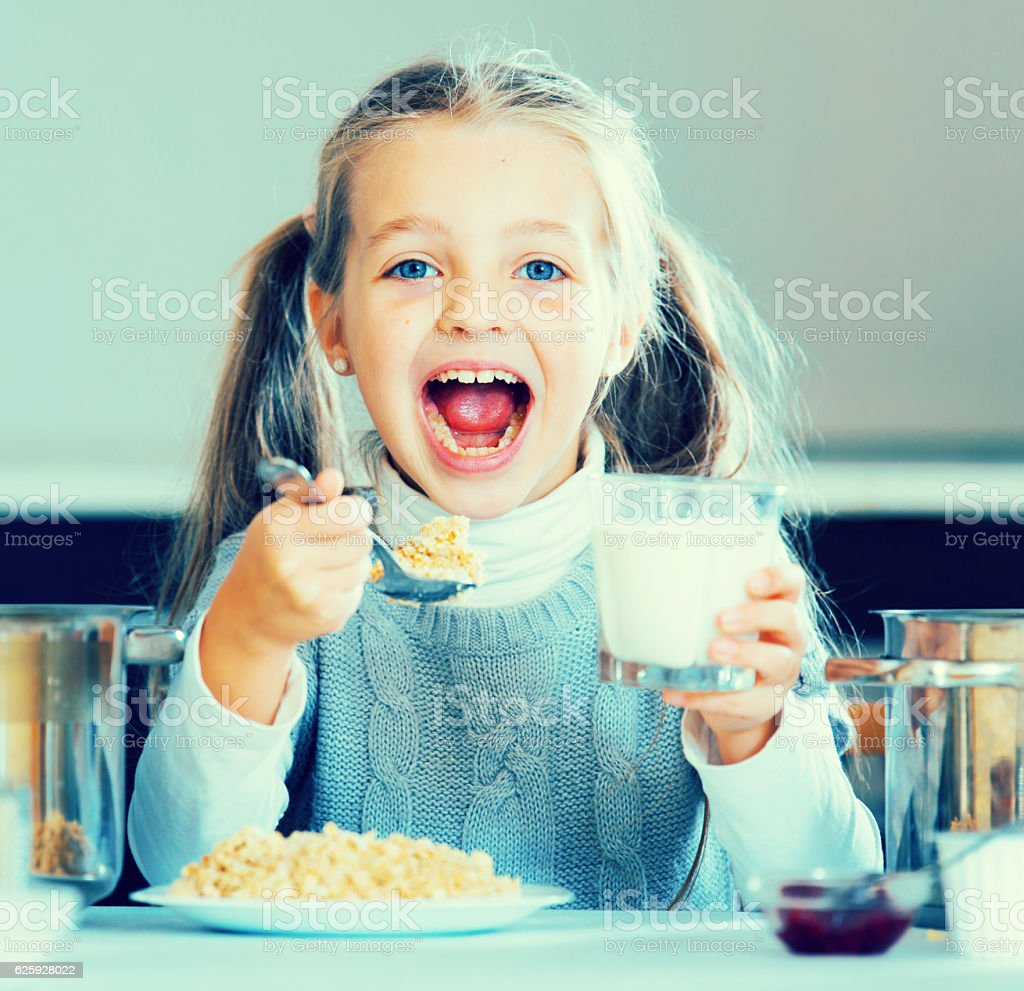 Hungry little girl with milk and oatmeal kasha stock photo