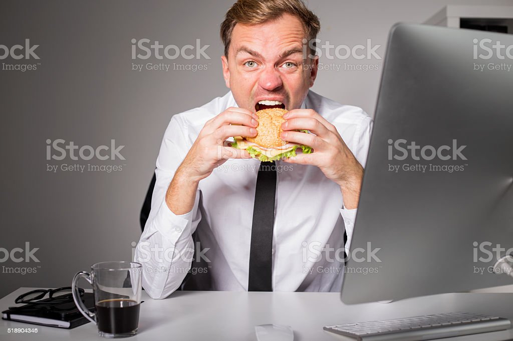 Hungry man at the office eating burger stock photo