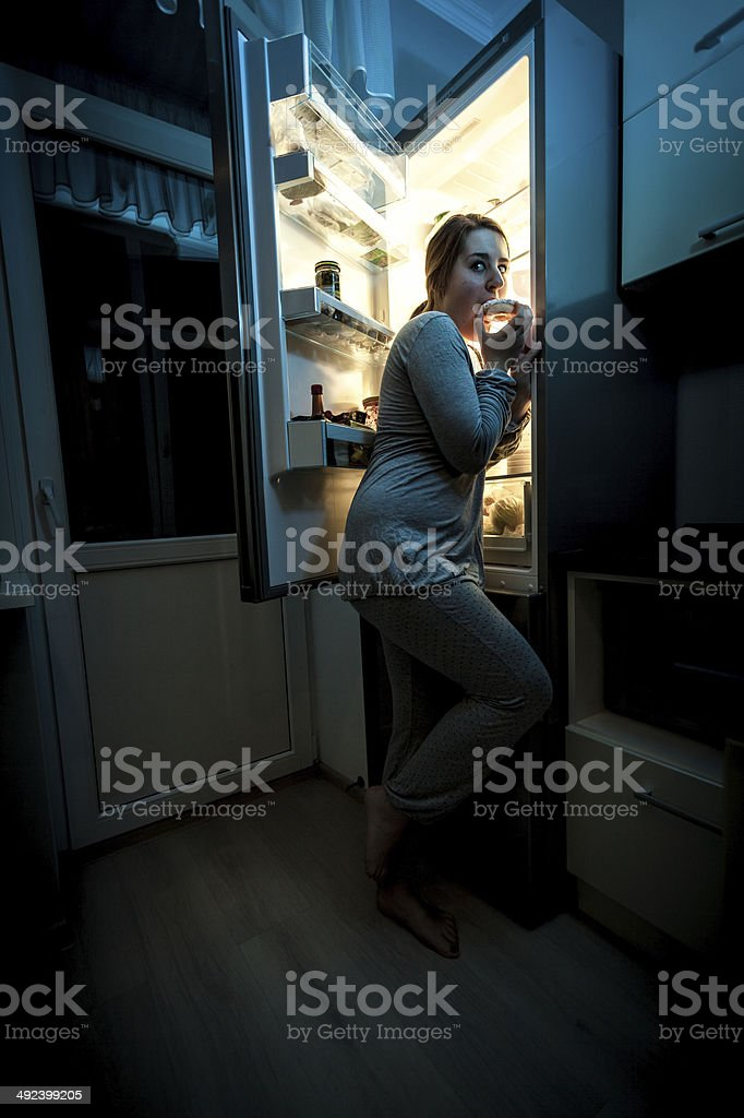 hungry woman eating at night near refrigerator stock photo