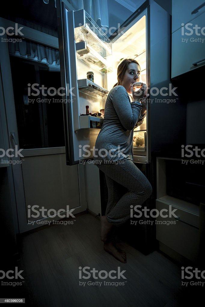 hungry woman eating at night near refrigerator stock photo