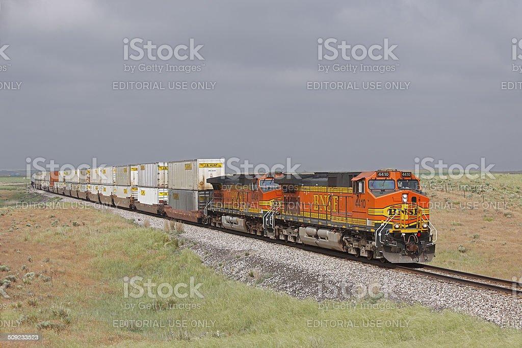 BNSF JB Hunt stack train with dark stormy sky stock photo