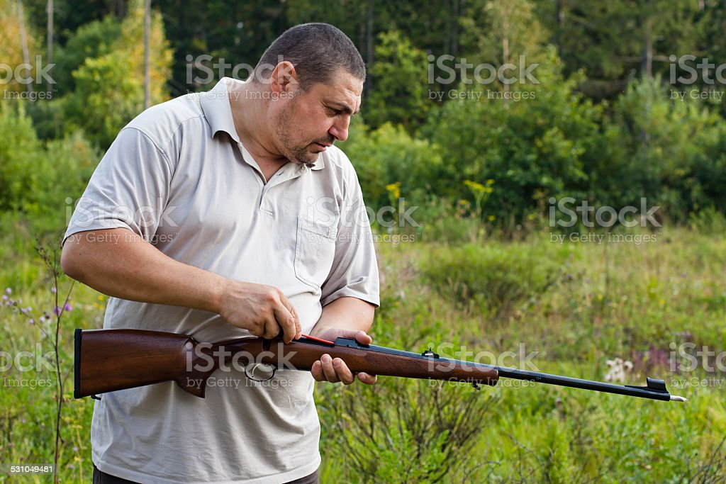 hunter cleans rifle stock photo