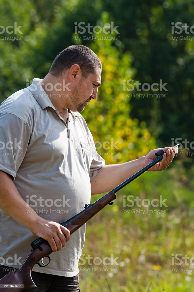 hunter cleans weapon stock photo