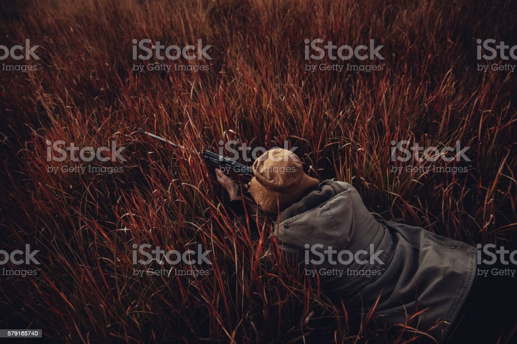 Hunter laying in high grass with rifle aiming on prey stock photo