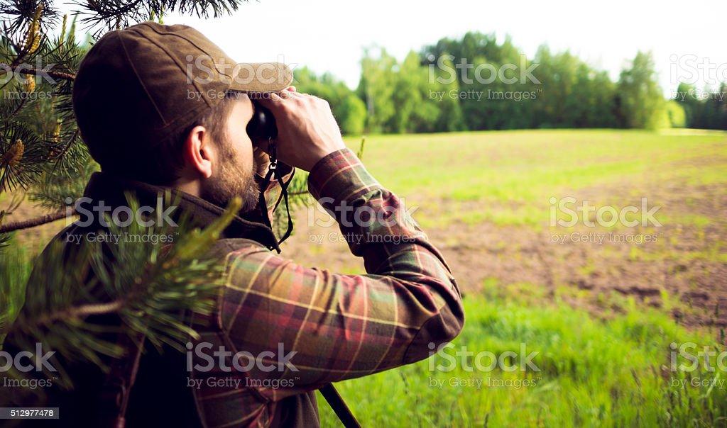 Hunter Looking Over The Field Through Binoculars stock photo