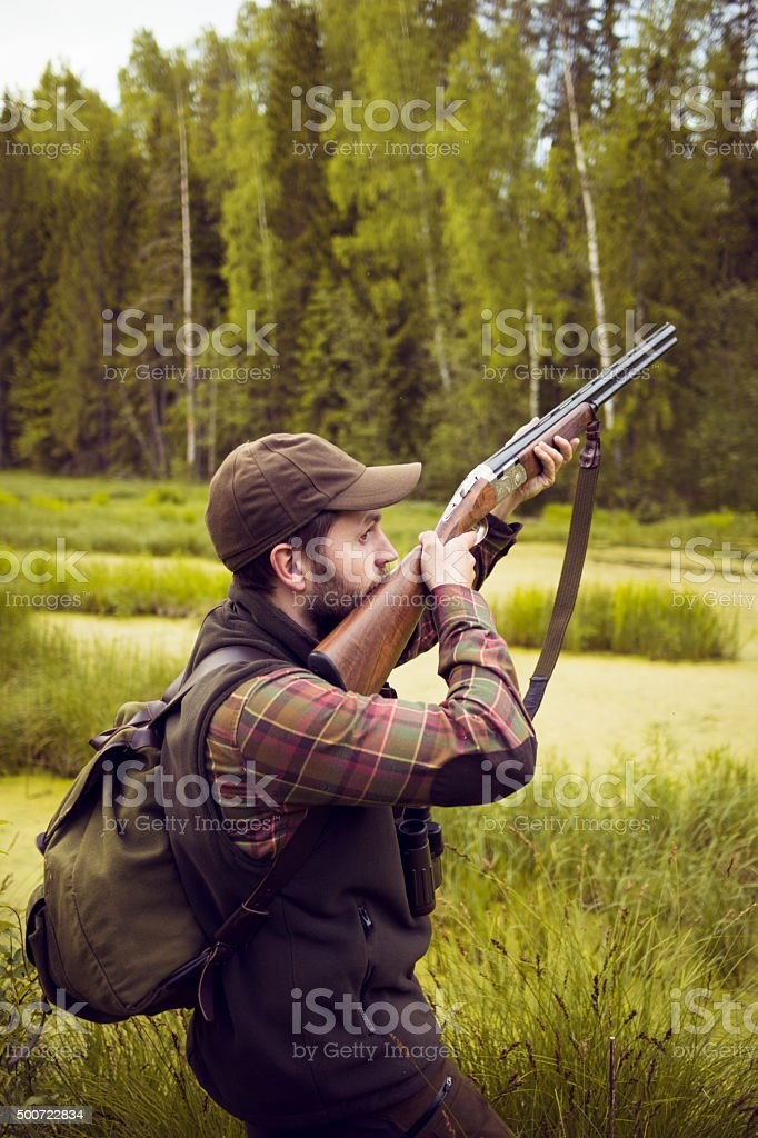 Hunter Man Aiming While Looking Out For Danger stock photo