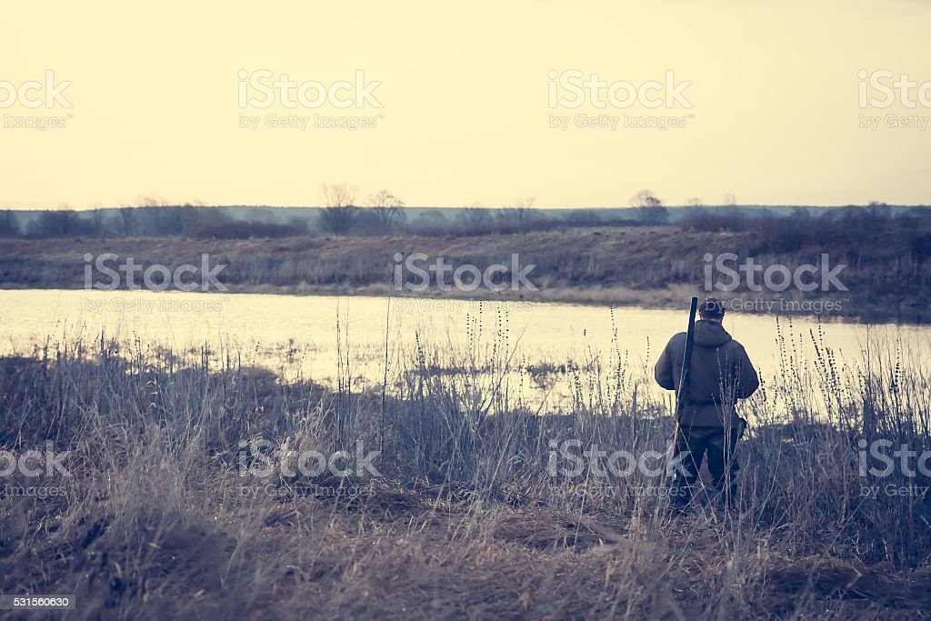 Hunter man at river bank in expectation of successful hunting stock photo