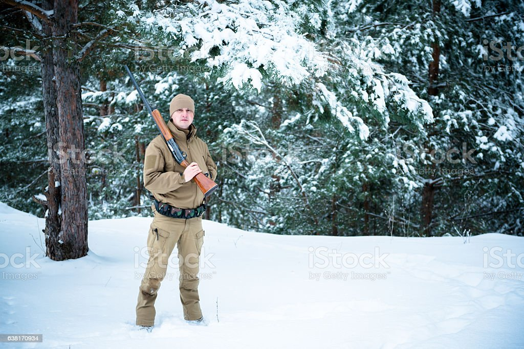 Hunter man dressed camouflage clothing standing in the winter stock photo