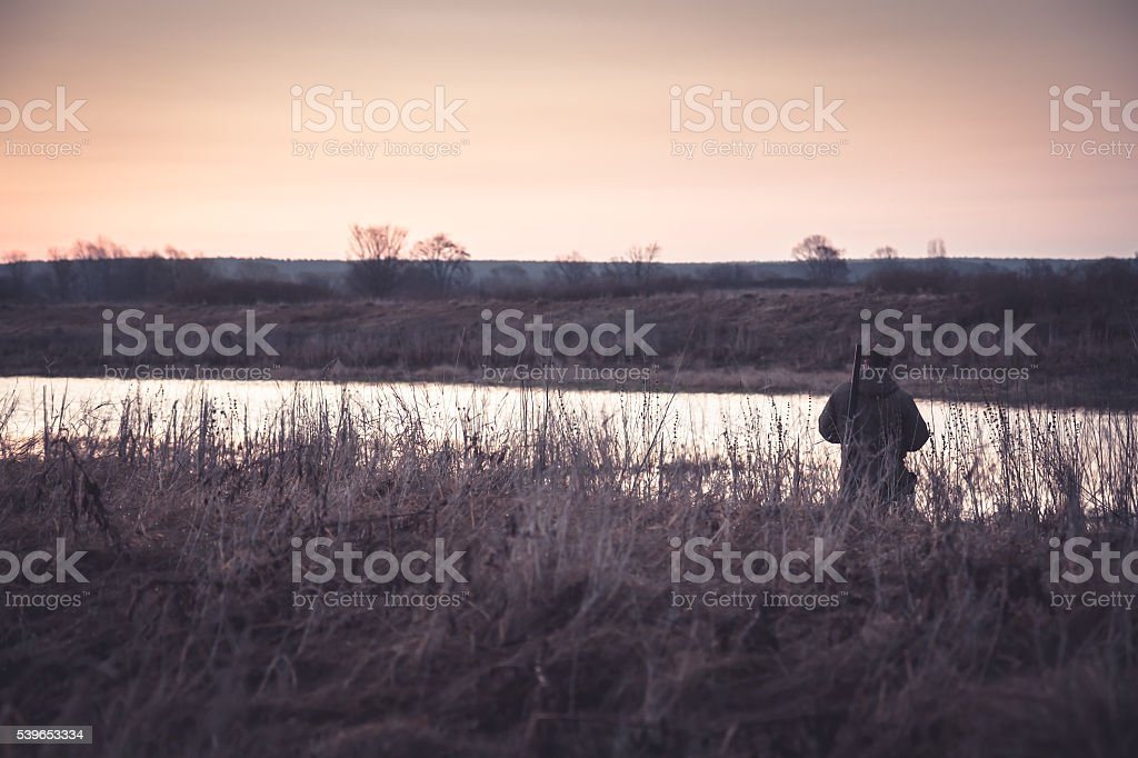 Hunter man in rural field during hunting stock photo