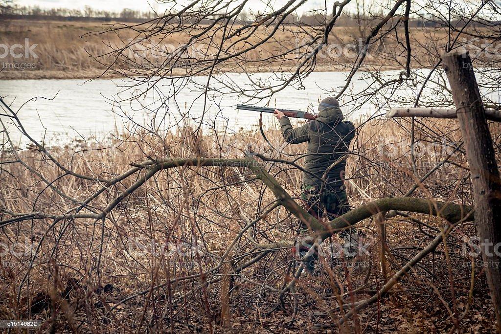 Hunter man with gun aiming and prepared to make shot stock photo
