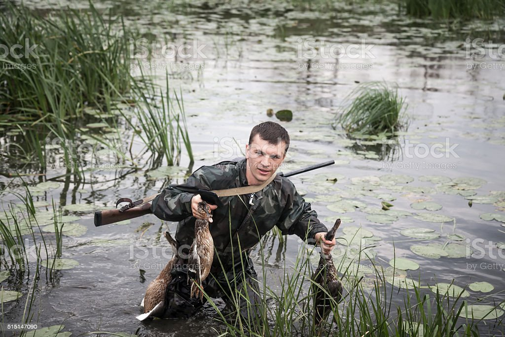 hunter man with prey after successful hunt break through marshland stock photo