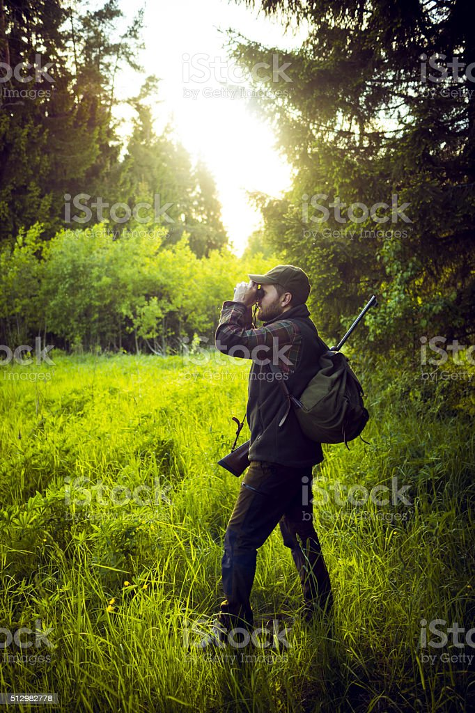 Hunter Observing The Distance With Binoculars In The Forest stock photo