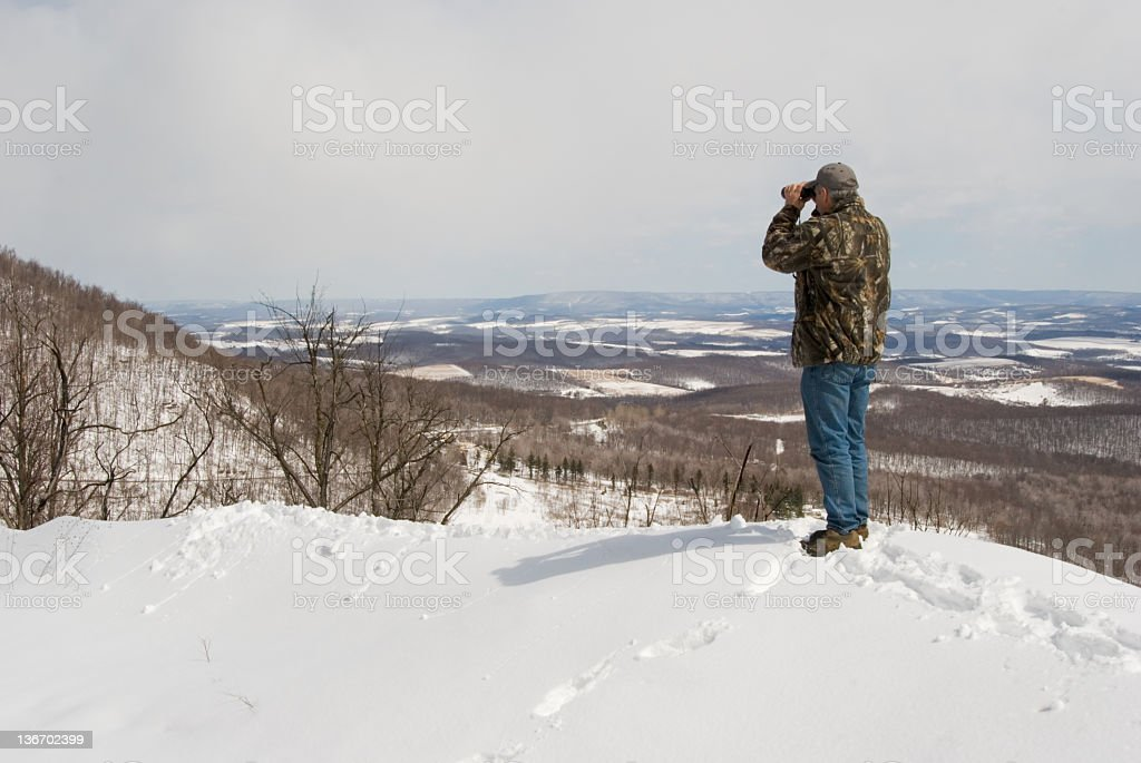 Hunter Searching with Binoculars From Snowy Mountain Top stock photo