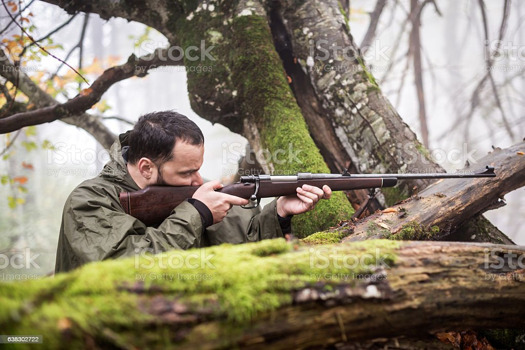 Hunter shooting from the rifle stock photo
