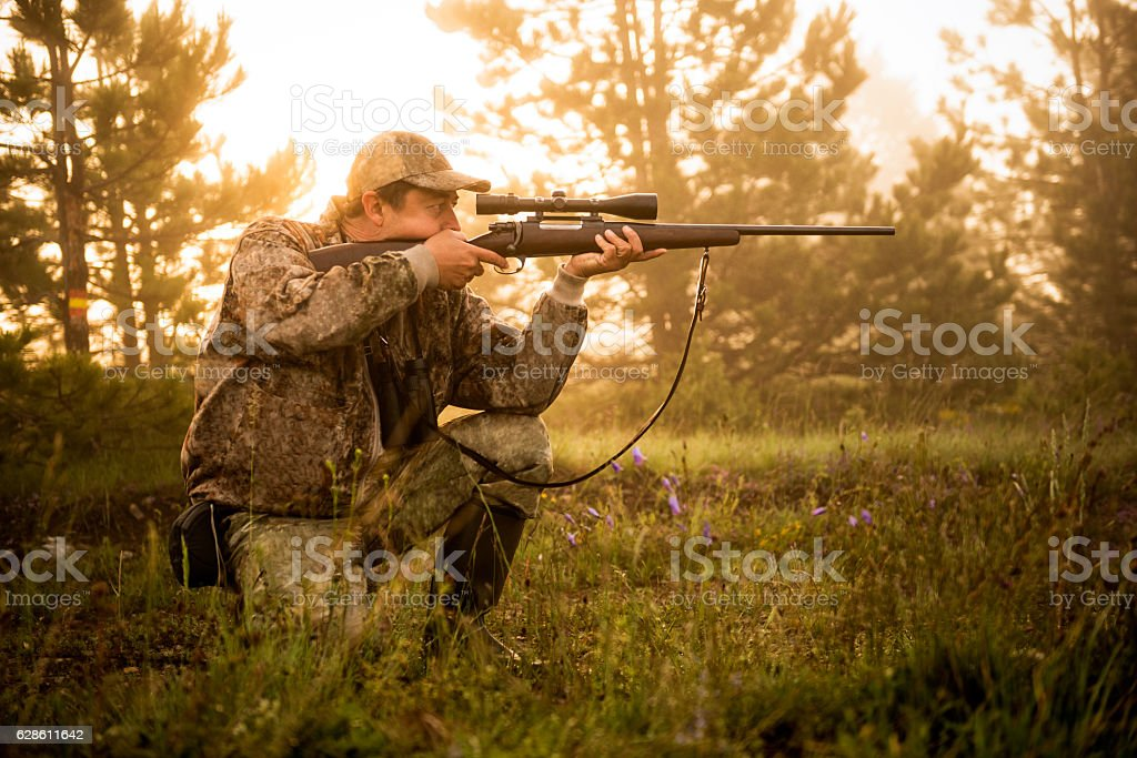 Hunter shooting with rifle stock photo
