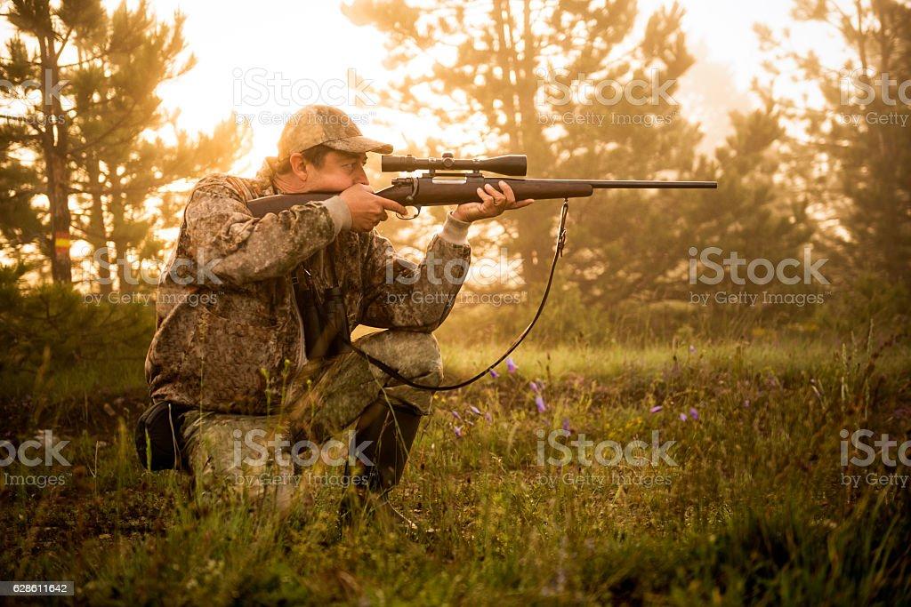 Hunter shooting with rifle stock photo