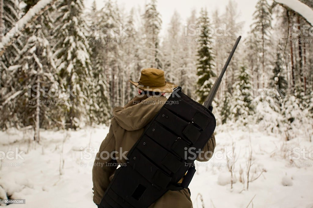 Hunter with Gun in Winter Forest stock photo