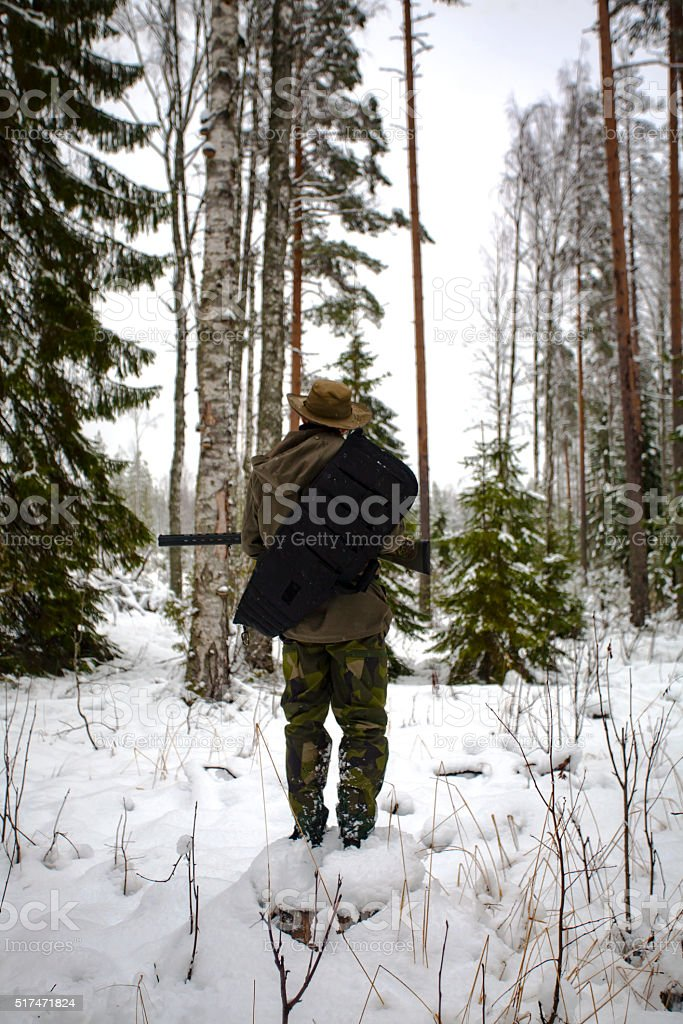 Hunter with Gun Standing on the Tree Stub stock photo