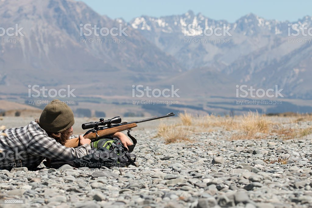 Hunter with riffle on background of mountains stock photo