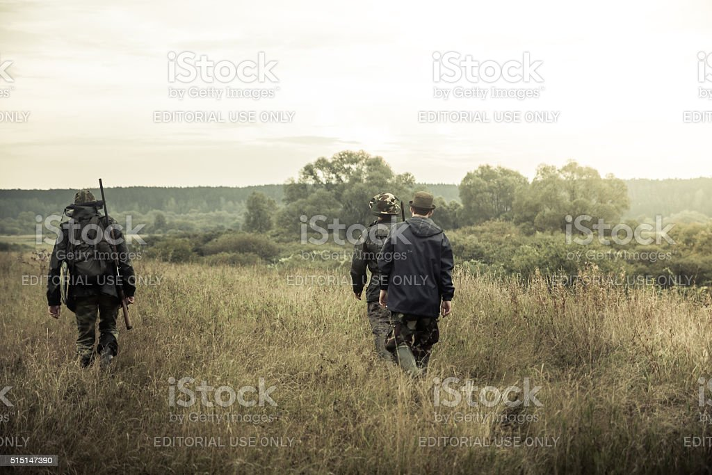 Hunters going on  rural field at sunrise during hunting season stock photo