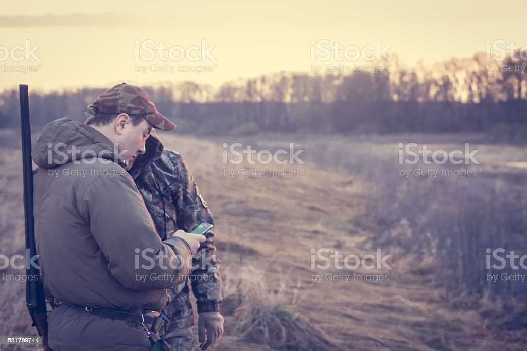 Hunters in rual field during hunting season holding smartphone stock photo