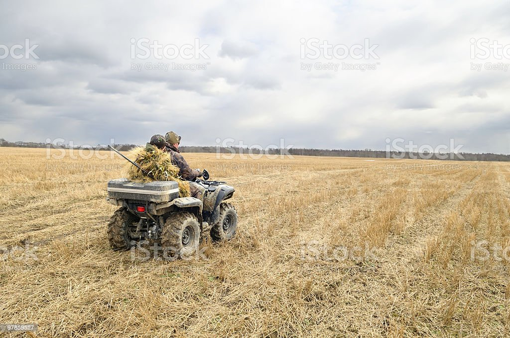 Hunters on quad bikes. stock photo