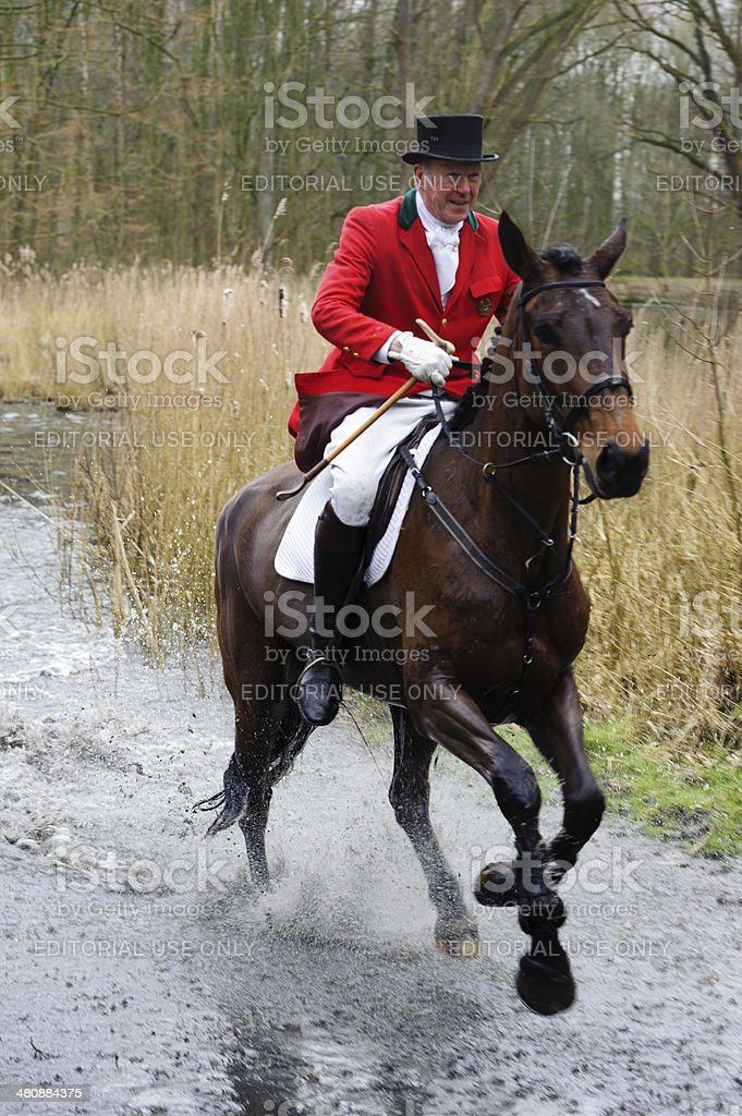 hunters riding their horses through a swamp royalty-free stock photo