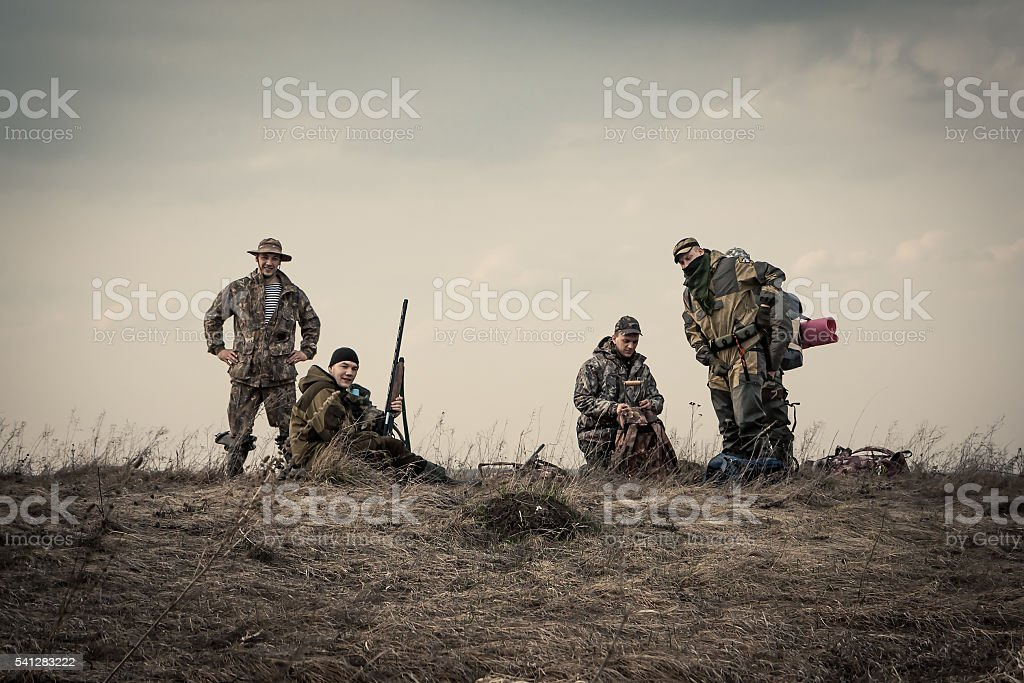 Hunters standing together against sunset sky  during hunting season stock photo