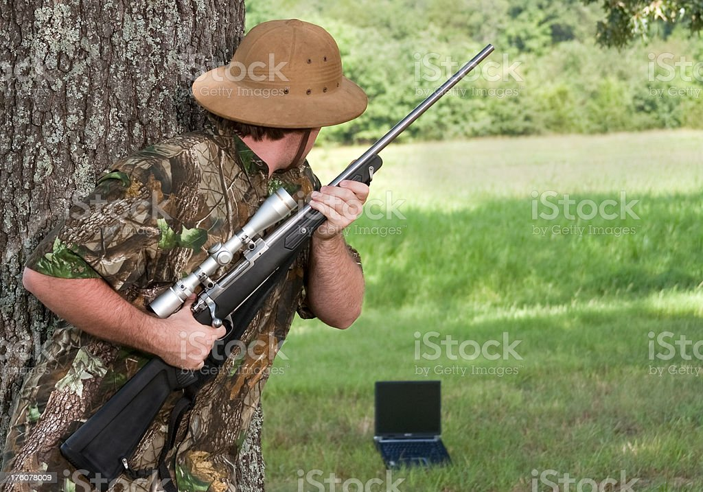 hunting a laptop computer with rifle stock photo