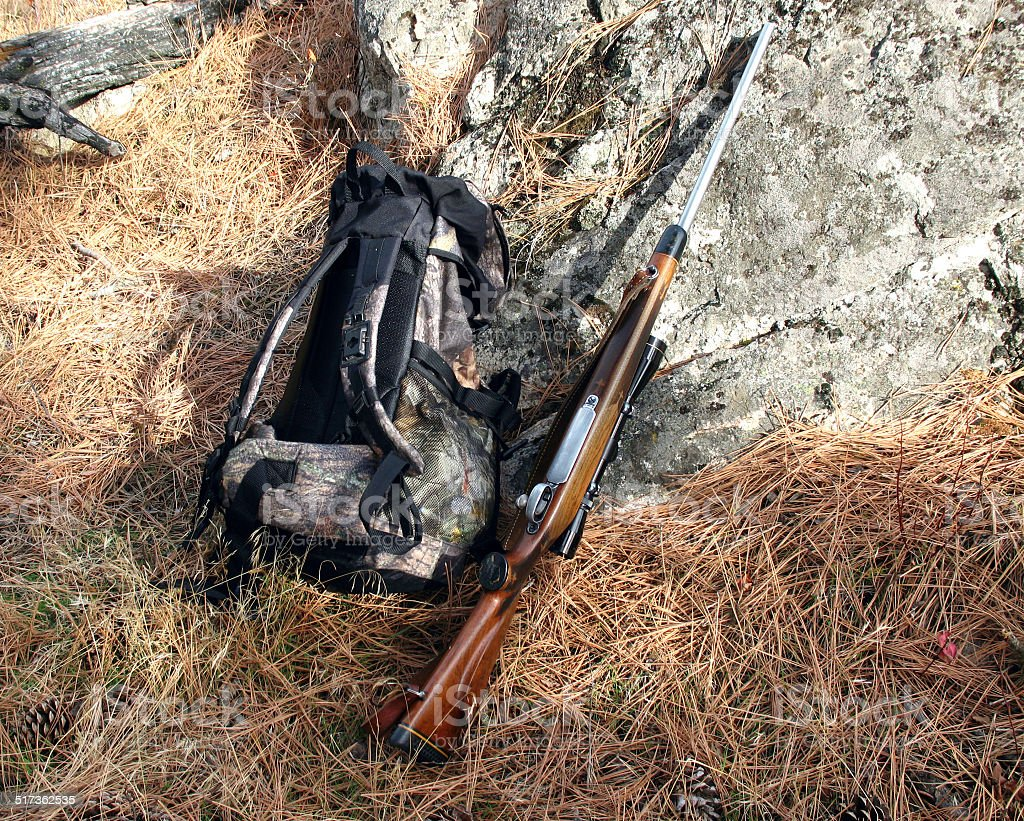 Hunting rifle and backpack against rock photo. stock photo