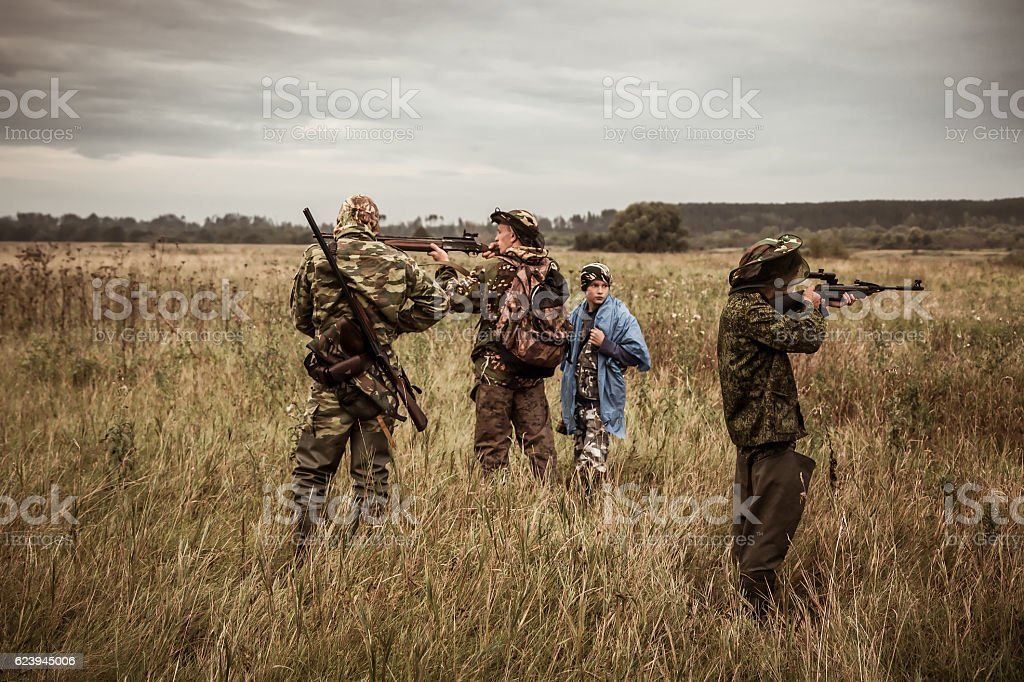 Hunting scene with hunters aiming during hunting season in field stock photo