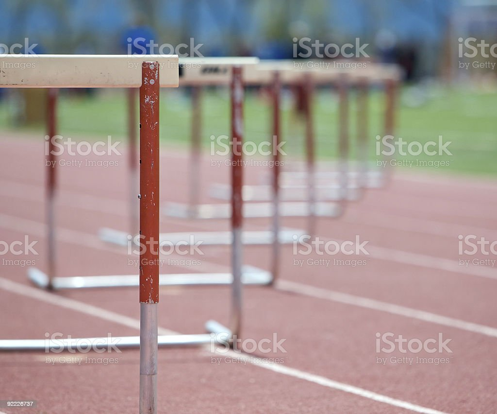 Hurdles lined up on a track, fading focus. stock photo