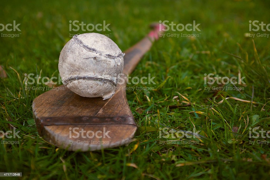 Hurling wooden stick and Sliotar ball on the grass stock photo