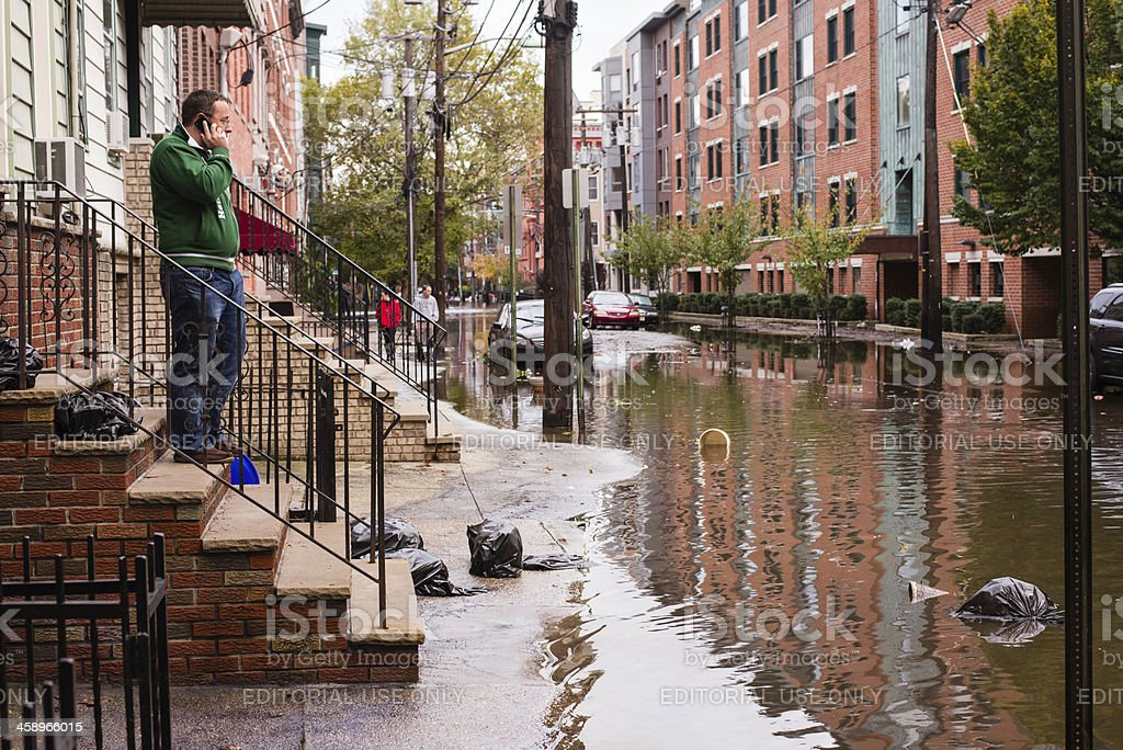 Hurrican Sandy: man talking on the phone near flooded street stock photo