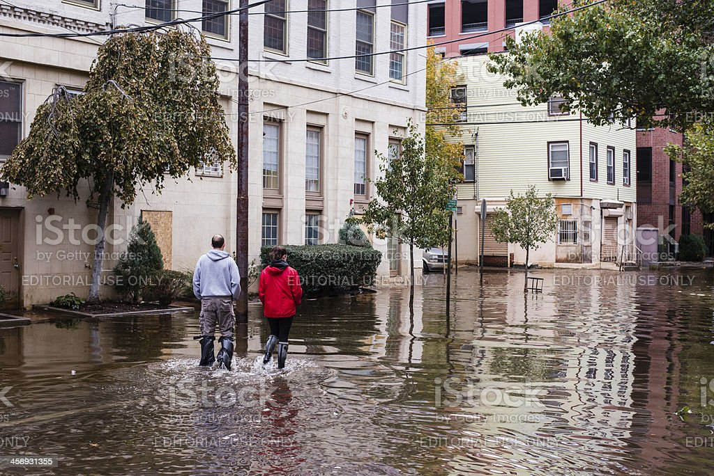 Hurrican Sandy: people walking on a flooded street stock photo
