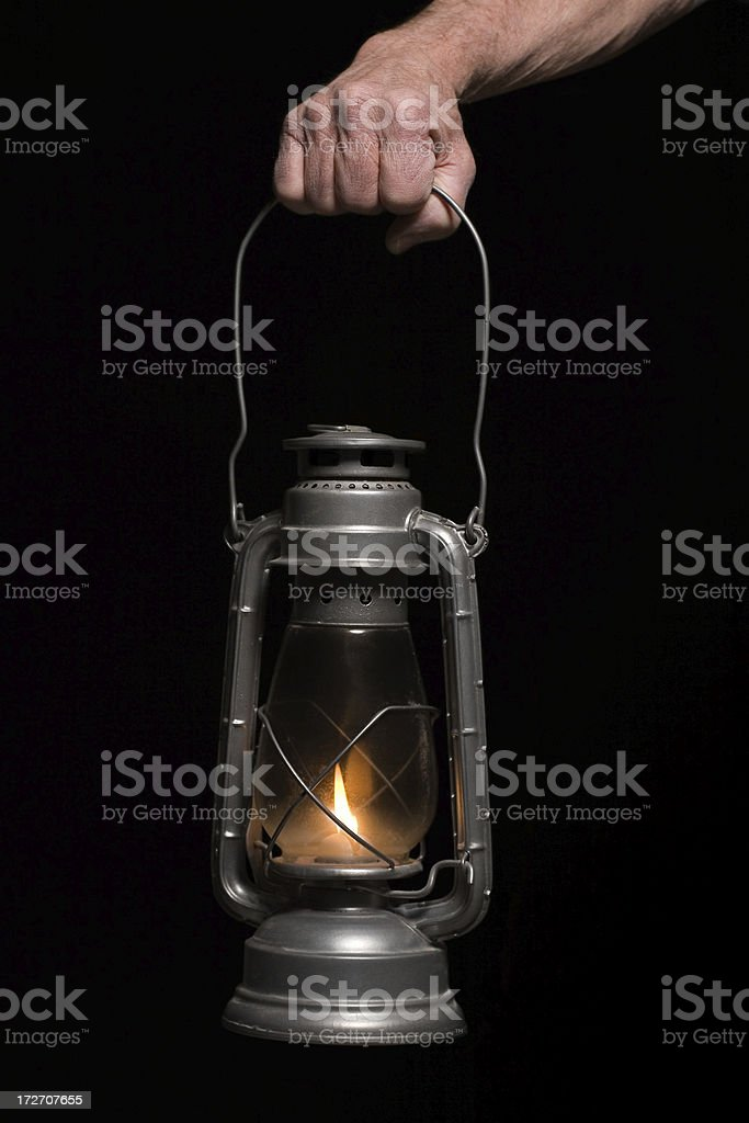 Hurricane Lantern with Flame Held by Hand on Black Background royalty-free stock photo