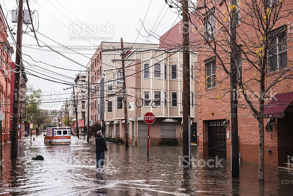 Hurricane Sandy: man standing on a flooded street stock photo