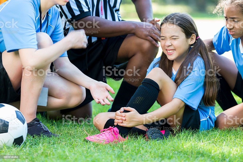Hurt girl soccer player holding onto her ankle stock photo