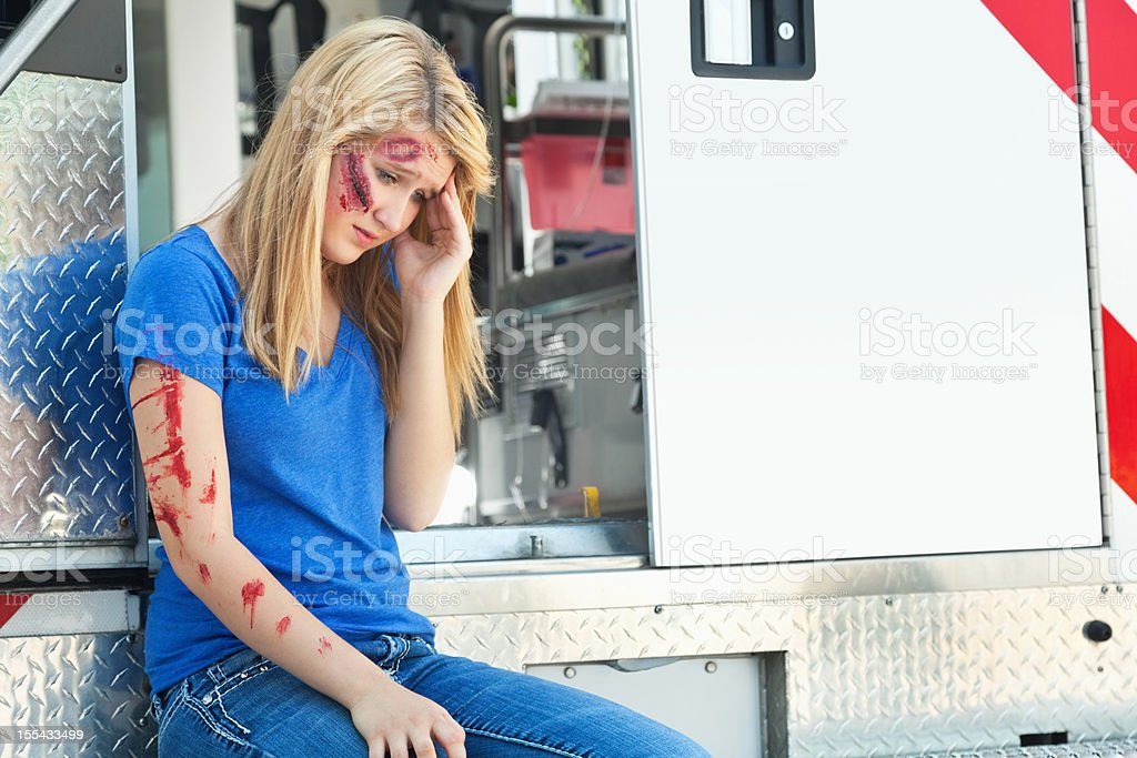 Hurt young girl sitting on ambulance at an accident scene royalty-free stock photo