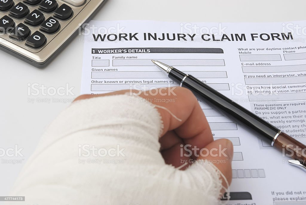 hurted hand and work injury claim form with pen  calculator stock photo